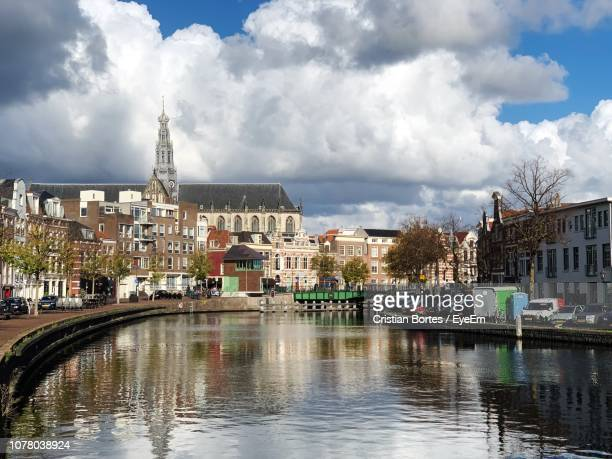 bridge over river amidst buildings in city against sky - bortes stockfoto's en -beelden