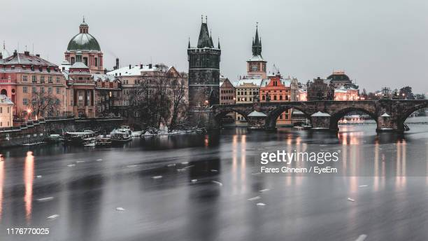 bridge over river amidst buildings in city - czech republic stock pictures, royalty-free photos & images