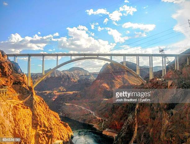 Bridge Over River Amidst Rocky Mountains Against Cloudy Sky