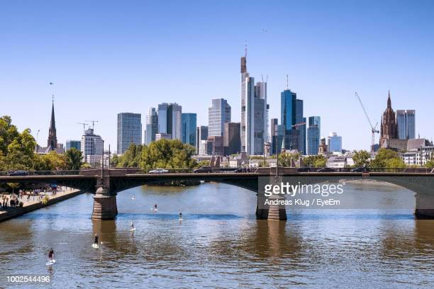 bridge over river by buildings against clear sky - frankfurt am main stock-fotos und bilder