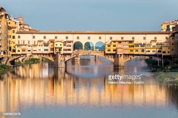 bridge over river by buildings against clear sky - ponte vecchio stock photos and pictures