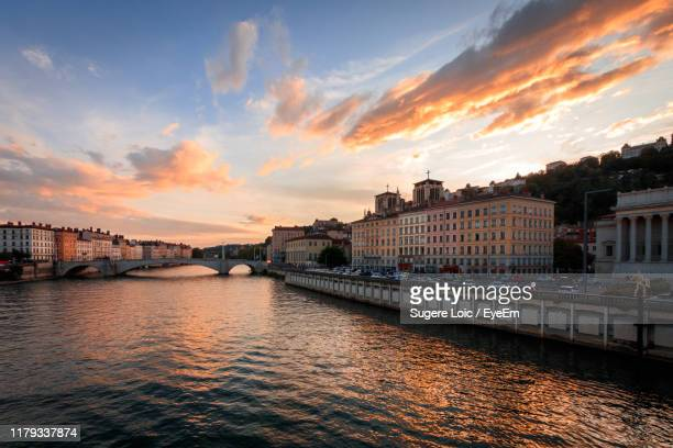 bridge over river by buildings against sky during sunset - rhone stock pictures, royalty-free photos & images