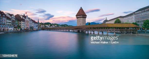 bridge over river by buildings against sky in city - spire stock pictures, royalty-free photos & images