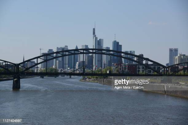 bridge over river by buildings against sky in city - agim meta stock pictures, royalty-free photos & images