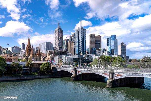 bridge over river by buildings against sky in city - 遊歩道 ストックフォトと画像
