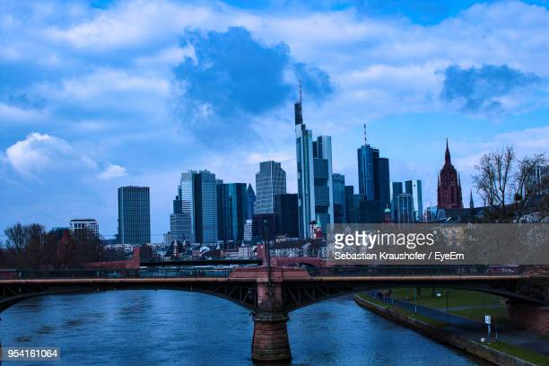 bridge over river by buildings against sky in city - sebastian kraushofer stock-fotos und bilder