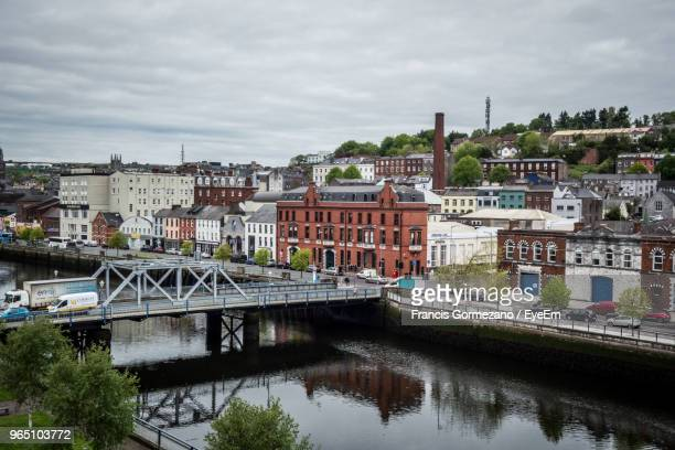 bridge over river by buildings against sky in city - cork city stock pictures, royalty-free photos & images