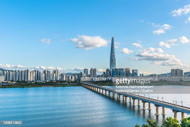 bridge over river by buildings against sky - seoul stock pictures, royalty-free photos & images