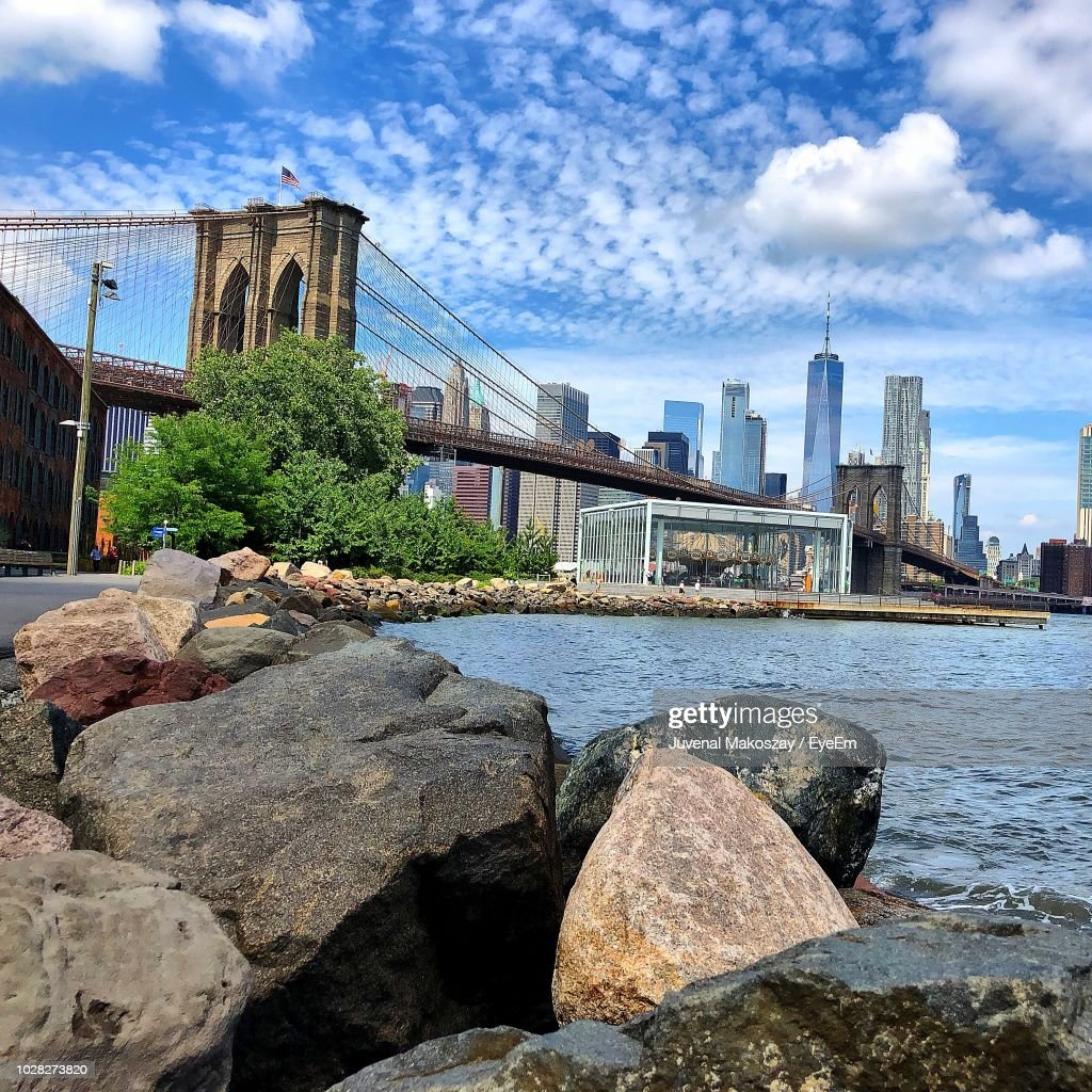 Bridge Over River By Buildings Against Sky : Stock Photo