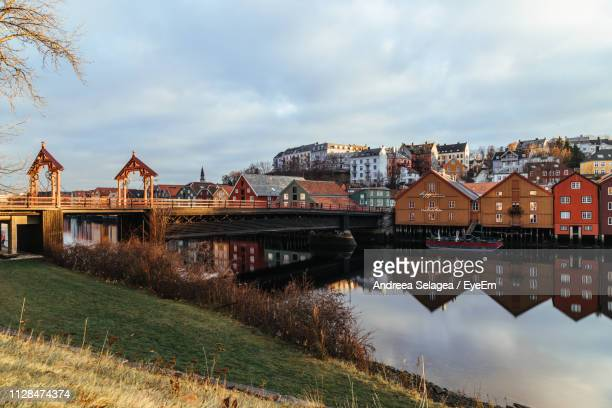 bridge over river by buildings against sky - トロンハイム ストックフォトと画像