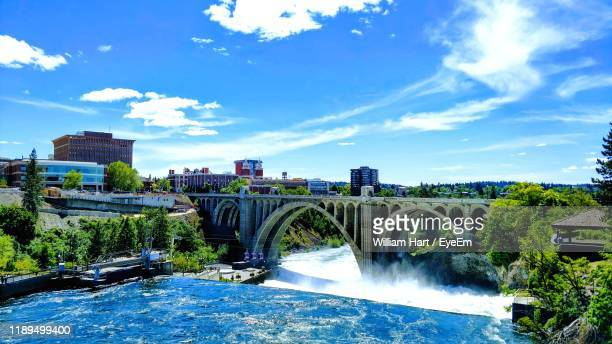 bridge over river by buildings against sky - spokane stock pictures, royalty-free photos & images