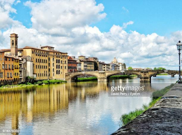 bridge over river by buildings against sky - florence italy stock pictures, royalty-free photos & images