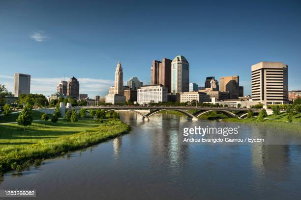 bridge over river by buildings in city against blue sky - columbus ohio stock pictures, royalty-free photos & images