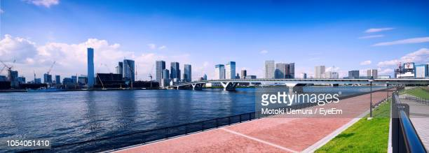 bridge over river by buildings in city against sky - kanto region stock pictures, royalty-free photos & images
