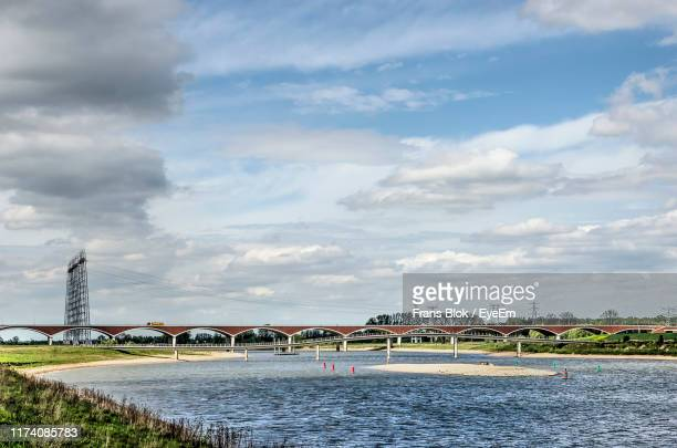 bridge over river by buildings in city against sky - nijmegen stock pictures, royalty-free photos & images
