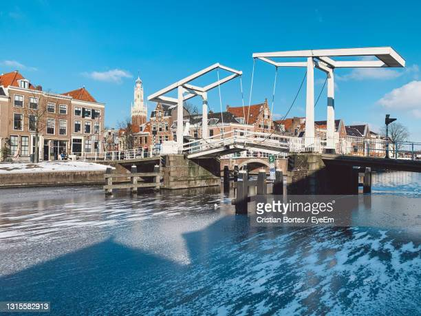 bridge over river by buildings in city against sky - bortes stock pictures, royalty-free photos & images
