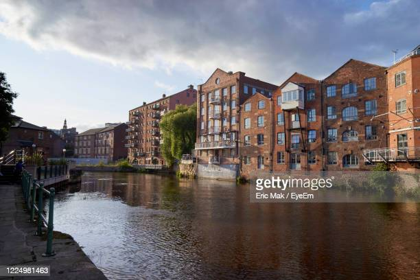 bridge over river by buildings in city centre against sky - leeds stock pictures, royalty-free photos & images