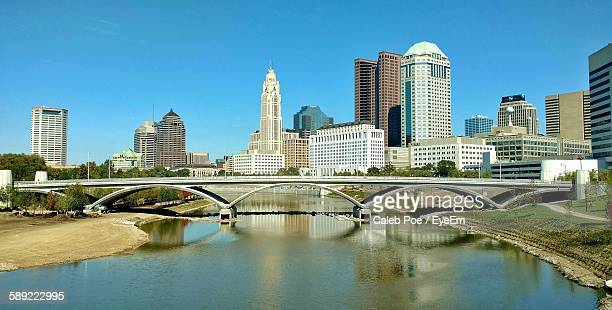 Bridge Over River By Cityscape Against Clear Blue Sky