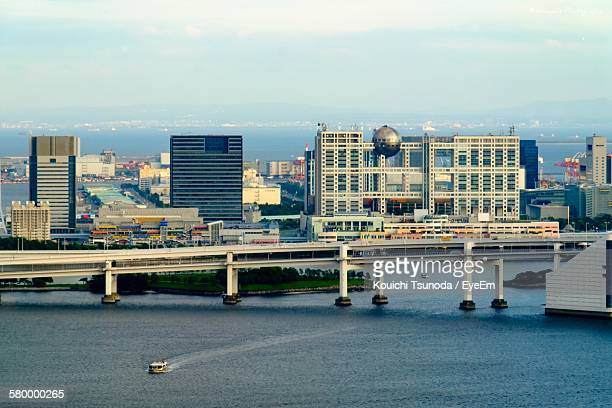 bridge over river by fuji television building against sky - fuji television stock photos and pictures