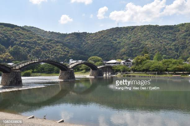 bridge over river by mountains against sky - 山口県 ストックフォトと画像
