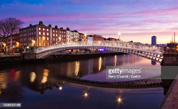 bridge over river in city against sky at dusk - dublin stock pictures, royalty-free photos & images
