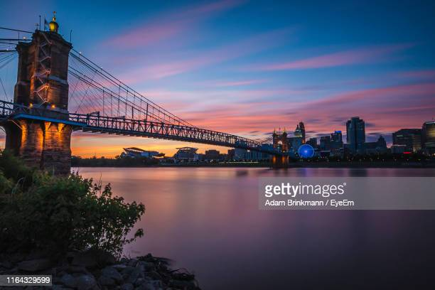 bridge over river in city against sky during sunset - cincinnati stock pictures, royalty-free photos & images