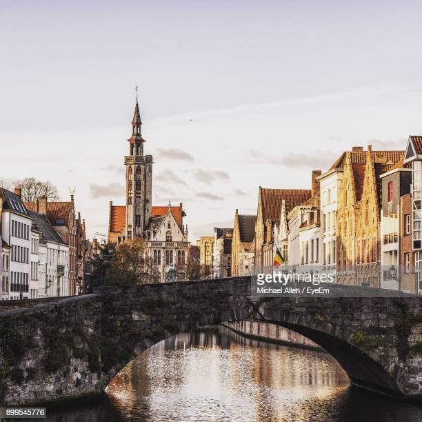 bridge over river in city against sky - bruges stock pictures, royalty-free photos & images