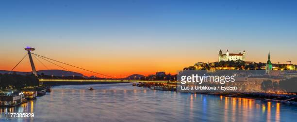 bridge over river in city at sunset - bratislava stock pictures, royalty-free photos & images