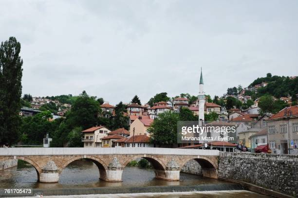 bridge over river in town against sky - sarajevo stock-fotos und bilder