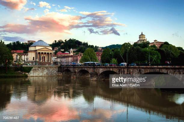 bridge over river with buildings in background - turin photos et images de collection