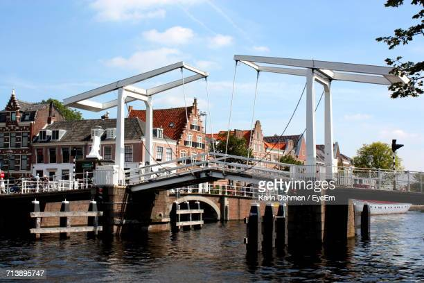 bridge over river with buildings in background - haarlem stock photos and pictures