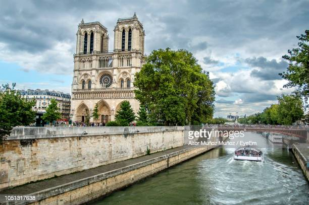 bridge over river with notre dame de paris in city - notre dame de paris stock photos and pictures