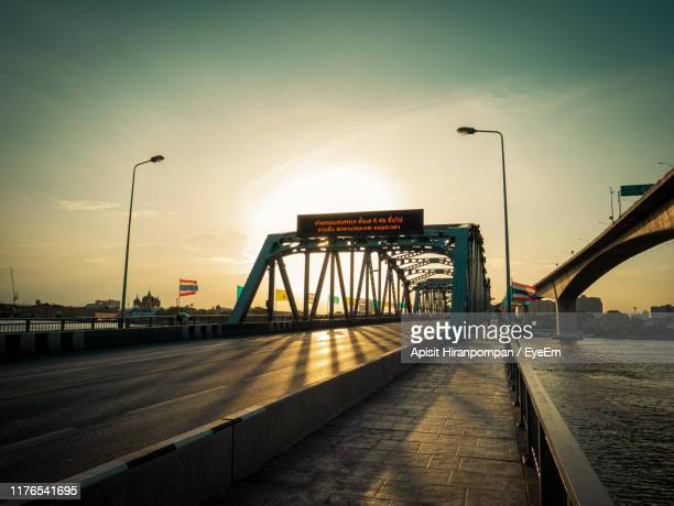 bridge over road against sky during sunset - apisit hiranpornpan stock pictures, royalty-free photos & images
