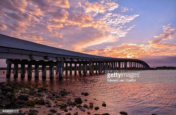 bridge over sea against cloudy sky at dusk - marco island stock pictures, royalty-free photos & images