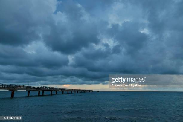 Bridge Over Sea Against Cloudy Sky