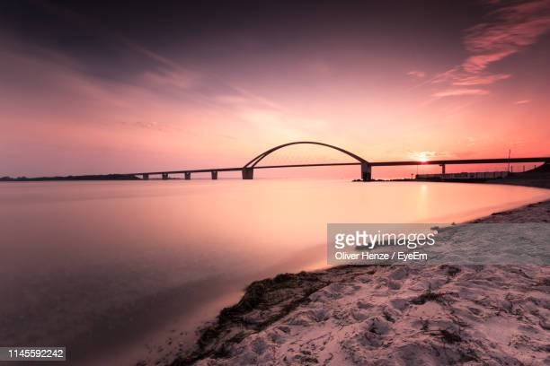 bridge over sea against romantic sky at sunset - fehmarn stock-fotos und bilder