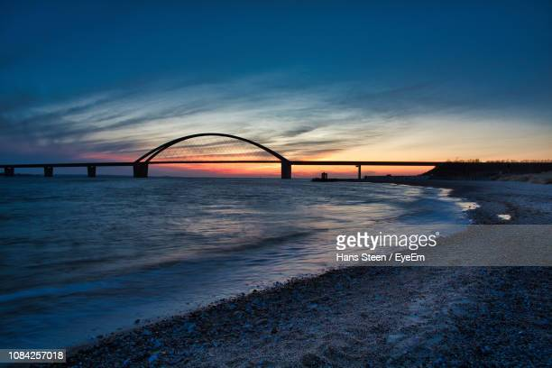 bridge over sea against sky at sunset - fehmarn stock-fotos und bilder