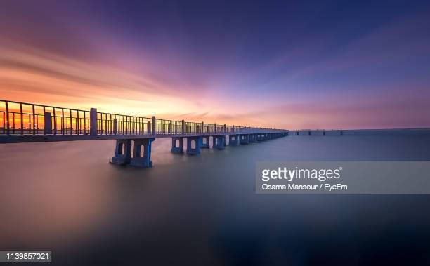 bridge over sea against sky during sunset - waterfront stock pictures, royalty-free photos & images