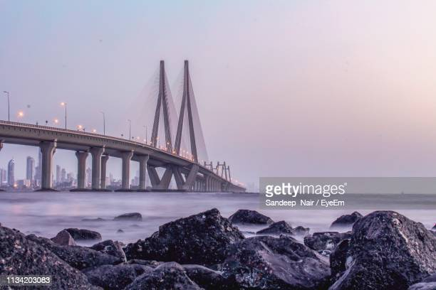 bridge over sea against sky - waterfront stock pictures, royalty-free photos & images