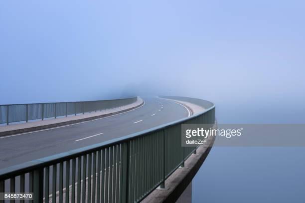 Bridge over Sylvenstein Reservoir disappearing in heavy fog, Sylvenstein Lake, Bavaria, Germany