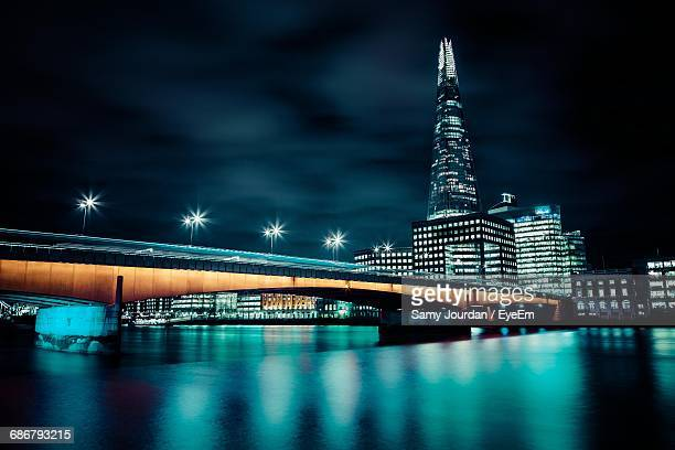 Bridge Over Thames River With Reflection Against Modern Buildings At Night