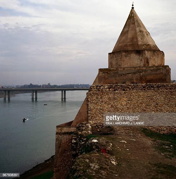 A bridge over the Tigris river in Mosul with the Mashhad Imam Yahya ibn alQasim mausoleum on the right Iraq