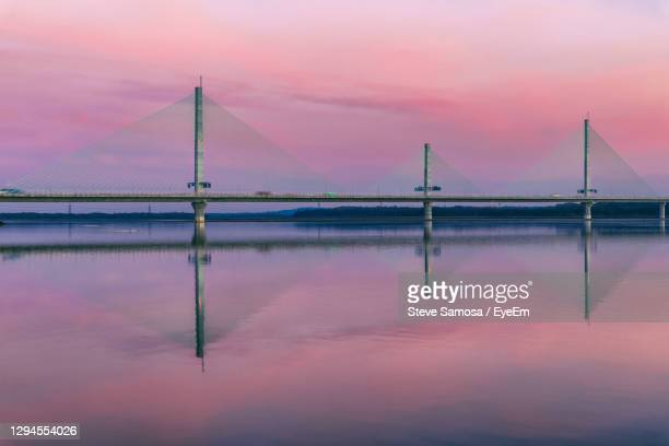 bridge over water against romantic sky at sunset - widnes stock pictures, royalty-free photos & images