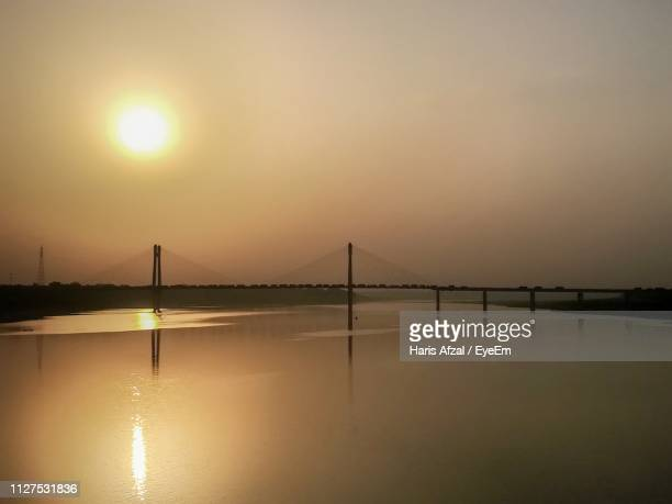 bridge over water against sky during sunset - prayagraj stock pictures, royalty-free photos & images
