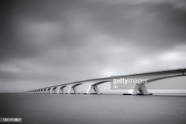 """bridge to nowhere over the calm sea with clouds above - """"sjoerd van der wal"""" or """"sjo""""nature stockfoto's en -beelden"""