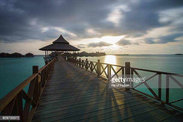 bridge & turquoise oceanic of mabul island, long exposure during sunrise view - mabul island stock photos and pictures