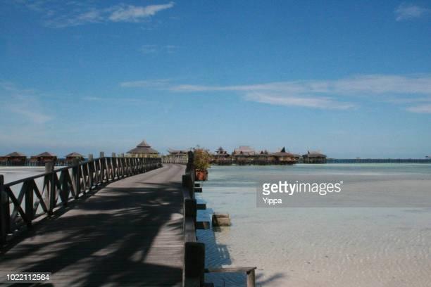 bridge & turquoise oceanic of mabul island - mabul island stock photos and pictures