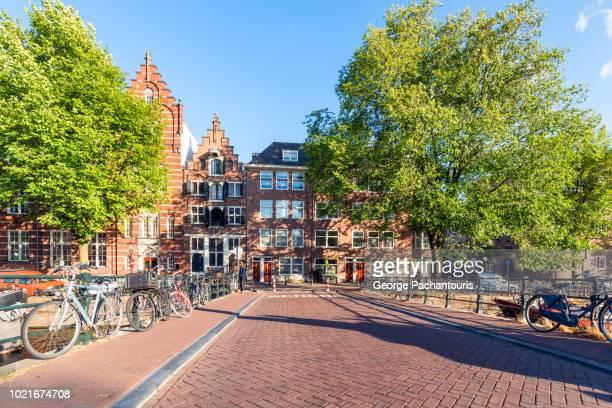 bridge with bicycles in amsterdam, netherlands - amsterdam stock pictures, royalty-free photos & images