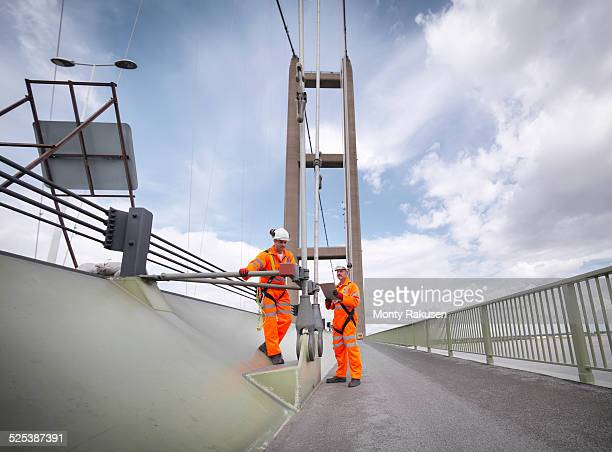 Bridge workers inspecting suspension bridge cables. The Humber Bridge, UK was built in 1981 and at the time was the worlds largest single-span suspension bridge