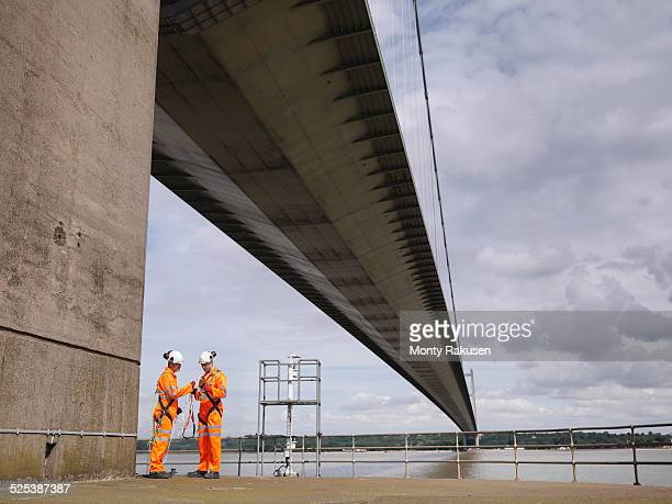 Bridge workers meeting under suspension bridge. The Humber Bridge, UK was built in 1981 and at the time was the worlds largest single-span suspension bridge